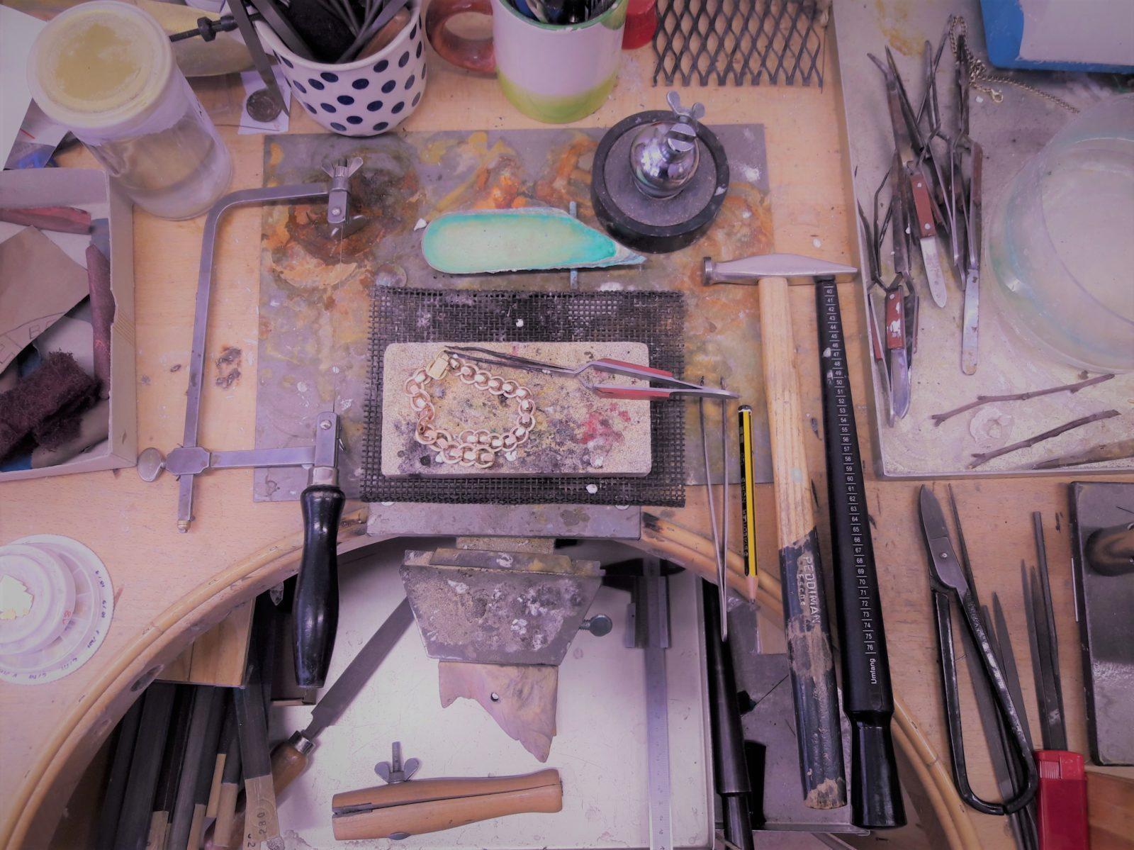 Blick von Oben auf einen Goldschmiede Werktisch mit Werkzeugen