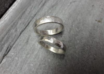 """Trauringe """"Findling"""" in Silber mit aufgerauhter Oberfläche sowie """"Libelle"""" mit Hammerschlag."""