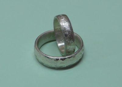 """Trauringe """"Kieselstein"""" mit rauer Oberfläche und """"Ruhiges Meer"""" in Silber."""
