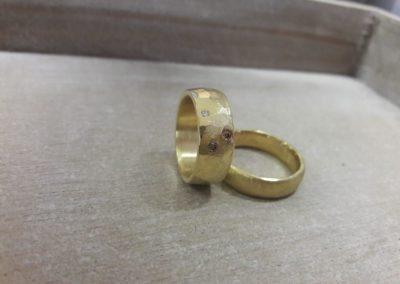 """Trauringe """"Libelle"""" halb poliert halb Hammerschlag in Gelbgold mit Brillanten und eismatt gewölbter Herrenring."""