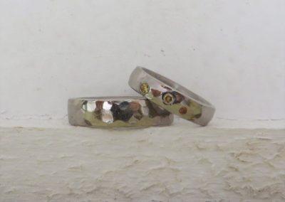 """Trauringe """"Libelle"""" als Hammerschlag in poliertem Weißgold mit bunten Brillanten in Braun und Goldfarben."""