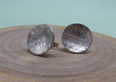 Ohrstecker aus gewölbten Silberschalen mit Struktur.