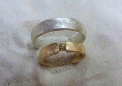 Schlichte zweifarbige Trauringe in Silber und Roségold in eismatt mit gelbem Brillanten.