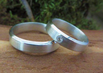 Trauringe in Silber mit Kanten in längsmatt mit Brillant.