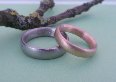 Zweifarbige Trauringe in Weißgold und Roségold mit schlichter matter Oberfläche.