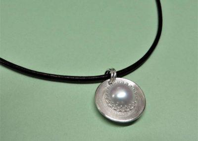 Perlanhänger aus Silber an Lederband.