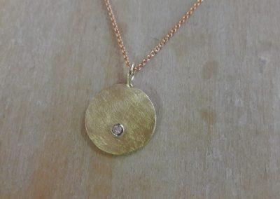 Runde Platte als Anhänger in eismattem Gold mit Brillant.