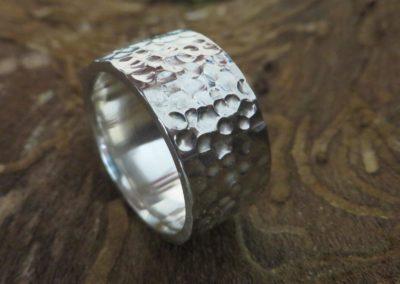 Breiter Silberring mit kugeliger Struktur.