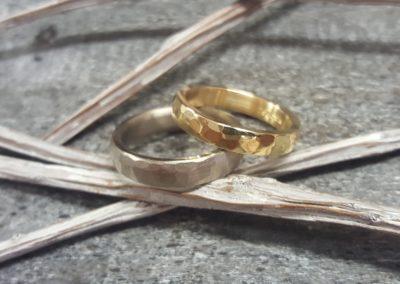 Gelbe und weiße Eheringe mit Hammerschlagmuster