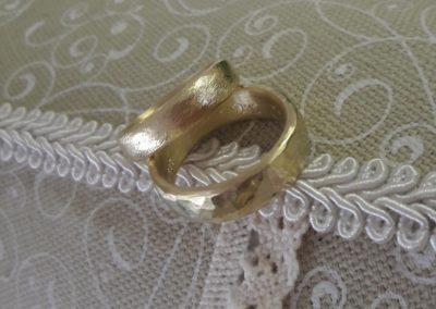 Damenring in Gold im Düne-Muster, Herrenring in Gold mit Hammerschlag im Libellenmuster.