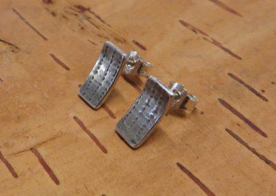 Kleine Ohrstecker aus Silber mit Struktur.