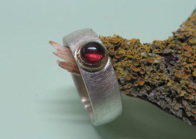 Silberring eismatt mit Granat in Goldfassung.