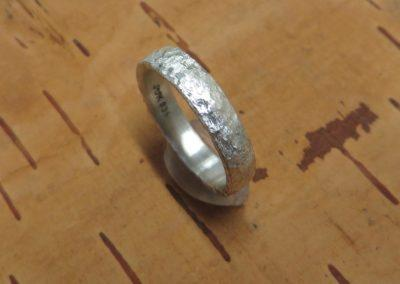 Silberring mit grober getupfter Struktur.