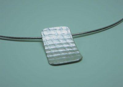 Silberanhänger mit Struktur an Silberreif.