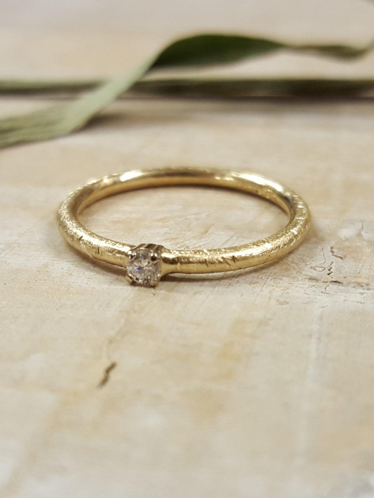 Verlobungsring in mattem Gelbgold mit weißem großen Brillanten.