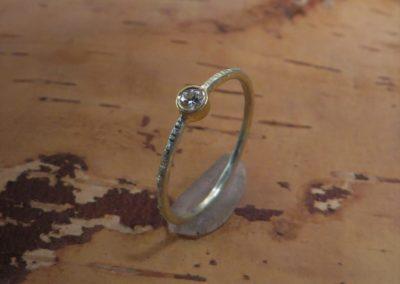 Zarter geschmiedeter Verlobungsring aus Gold mit naturfarbenem Brillant.
