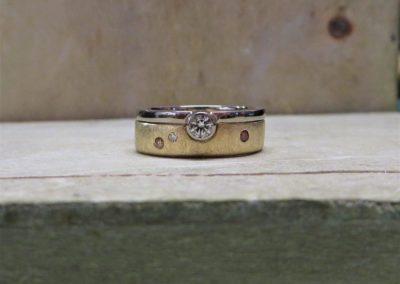 Verlobungsring, Vorsteckring aus Weißgold mit Brillant, der in den Trauring greift.